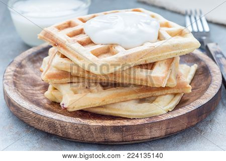 Homemade savory belgian waffles with bacon and shredded cheese, served with plain yogurt, on a wooden plate, horizontal