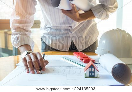 Architects are designing the house,Left hand holding house plan on chest,Model house, ruler, water level placed ,house model place on house plan with safety helmet placed side by side.