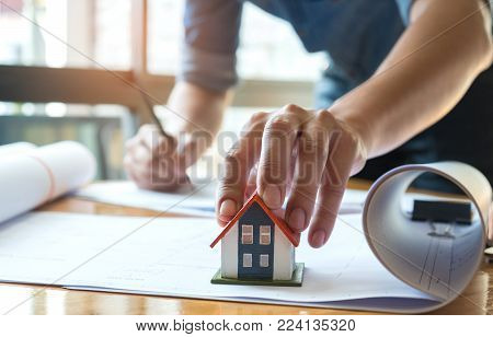 Architects are writing home,left hand catches on model house red roof,house plan roll is placed on the desk,Home design ideas.
