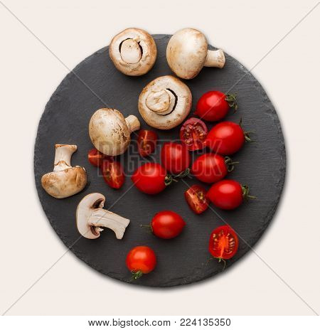 Cut tomatoes and mushrooms on rustic slate stone plate isolated over white background. Cooking healthy food, copy space, top view, cutout