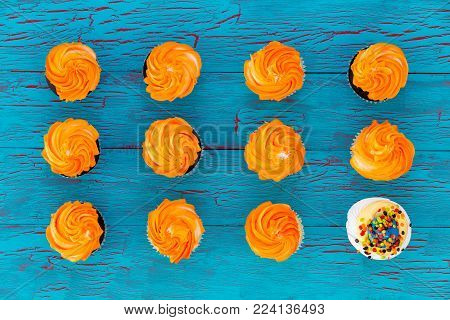 Still life of colorful cupcakes with orange twirled icing arranged in neat rows with one lone white cupcake with sprinkles in a conceptual image viewed from above on blue wood