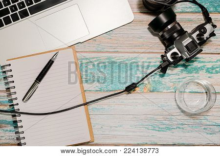 Photographer workspace - laptop, vintage DSLR camera wired to computer, notepad with pen and glass of water on vintage style rough painted wooden table. Freelancer home office concept. Top view.