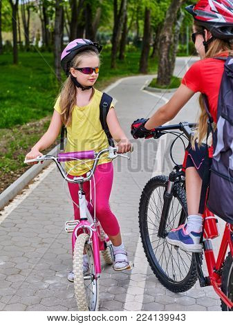Bikes bicyclist girl. Girls wearing bicycle helmet and glass with rucksack ciclyng bicycle. Walking in spring is good for your health. Bike share program save money and time at city street.
