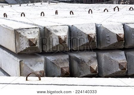 Stack of prestressed concrete piles on ground for foundation construction work. The process of construction of the embankment for protecting riverbank collapse by concrete foundation piles.