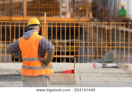 Confused worker in orange at the reconstruction area