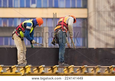 Two labours with hammers build scaffolding at the construction site