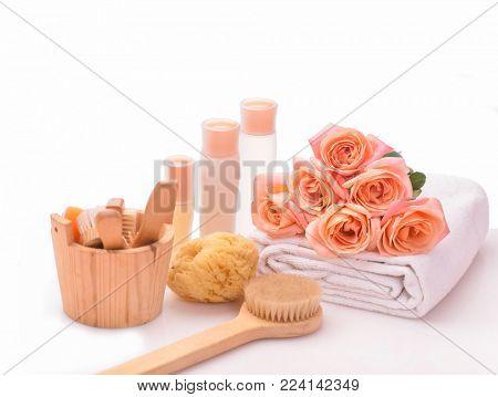 , Spa bath sitting with orange rose ,bath item in wooden bowl , towel, bottle oil, candle,