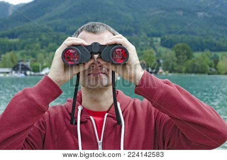 A middle-aged man with a binoculars observing nature at the lake on a cloudy day