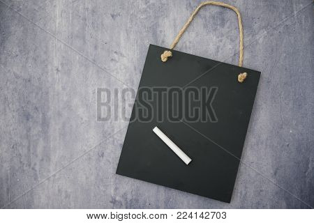Black chalk board with a stick of chalk on a blue slate background, taken with copy space