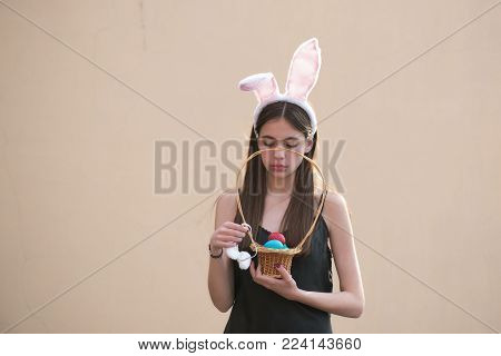 Easter Woman Holding Wicker Basket With Colored Eggs. Woman With Rosy Bunny Ears On Beige Background