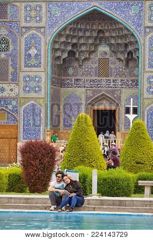 Isfahan, Iran - April 24, 2017: Young Iranian lovers hugs on a date near the mosque on a clear sunny day, the Naqsh-e Jahan Square.