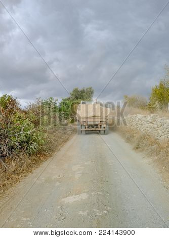 Narrow track with back view of lorry transporting large rocks in the countryside in Cyprus.