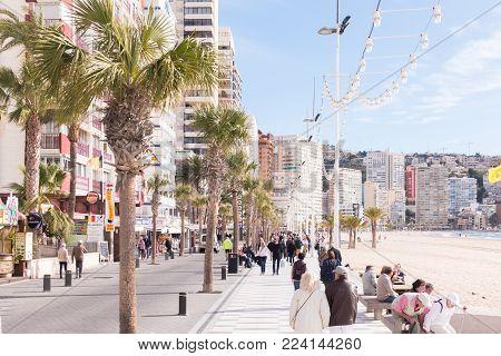 Benidorm, Spain - January 14, 2018: People walking on the Levante beach embankment street in Benidorm, Spain.