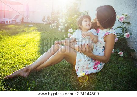 Nurturing And Future. Mothers Day Concept. Woman With Baby Girl Sitting On Green Grass. Family Love