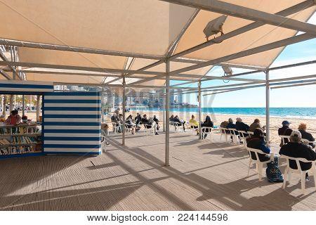 Benidorm, Spain - January 14, 2018: People resting in public Benidorm Beach Library area.