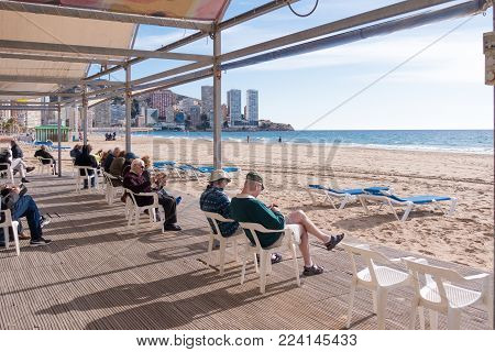 Benidorm, Spain - January 14: People resting, reading and playing chess in public Benidorm Levante Beach Library January 14, 2018