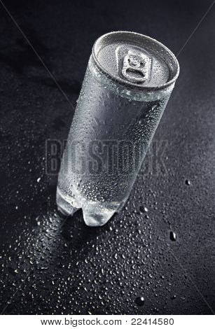 can with water droplets   on black background
