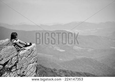 Pretty Brunette Thoughtful Girl With Long Hair In Blue Lace Dress Sitting On Stone Rock Cliff Lookin
