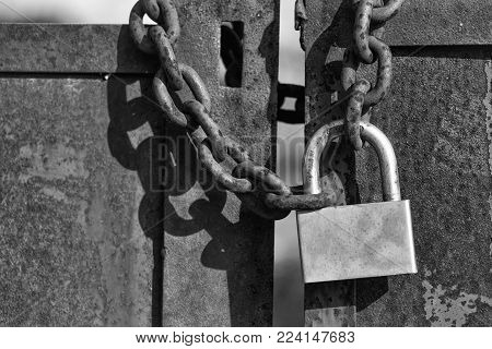 Padlock With Shackle And Locking Mechanism Closeup One Portable Lock On Chain On Unpainted Rusty Met