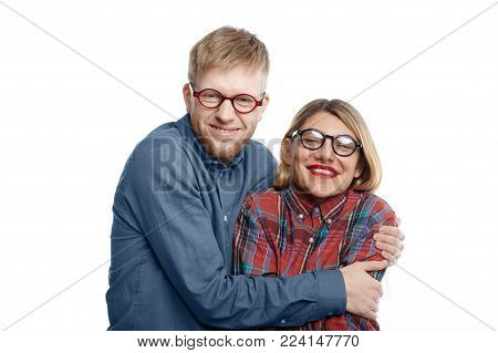 Portrait of extraordinary comic young Caucasian couple in eccentric clothes and eyewear having fun: geeky man with stubble hugging tight his happy attractive girlfriend with red lips and fair hair