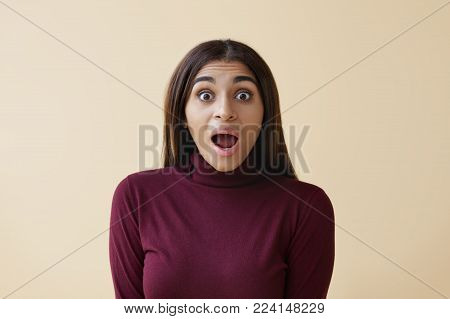 Isolated shot of beautiful Afro American woman with loose straight hair opening mouth widely, being lost for words, having surprised look, shocked with big sale prices or astonishing information