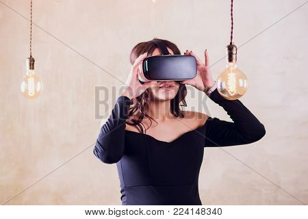 Girl use modern virtual reality glasses for mobile game application.Use mobile apps, play video games everywhere.Close up, focus on vr headset in woman hands.Trendy new augmented reality gaming device