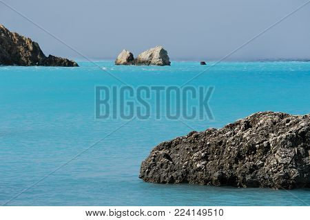 Seascape of the blue sea coast of the Ioannic Sea in Greece. Laconism and beauty of the Greek prophets. Sea and rocks. Tropical shades