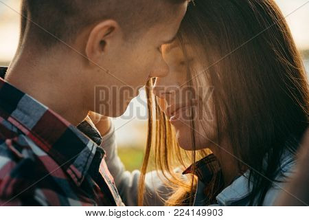 Sensitive romantic portrait of the cheerful couple in love rubbing noses during the sunset
