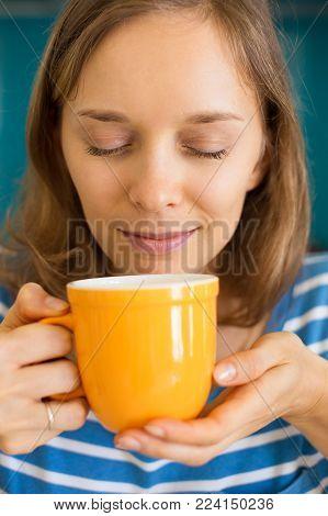 Closeup portrait of content young beautiful woman smelling tea aroma from cup with her eyes closed. Tasty tea concept. Front view.
