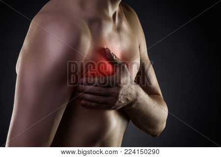Heart attack, man with chest pain on black background with red dot