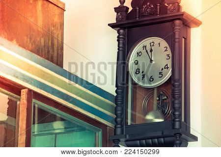 Close up of old vintage wall clock or winding clock hang on vintage wall. Manual winding clock in Chinese style with in asian house.