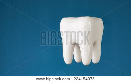 ermet ceramic tooth model isolated on blue background with copy space, close-up. Dental health, oral care, teeth restoration and 3d teeth whitening concept