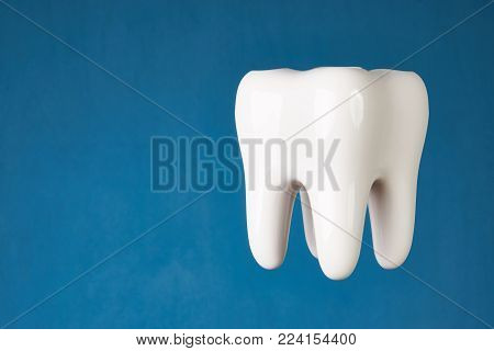 Ceramic tooth model isolated on blue background with copy space, close-up. Dental health, oral care, teeth restoration and 3d teeth whitening concept poster