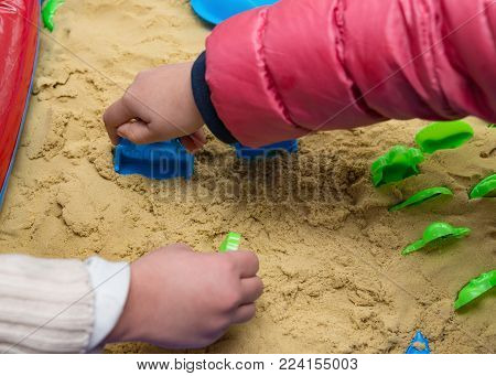 kids playing sand and plastic moulds horizontal