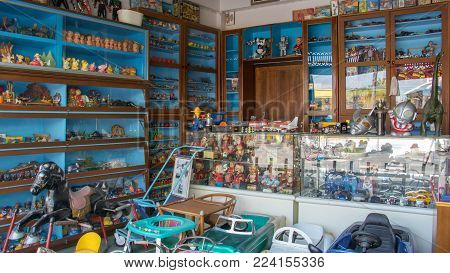 Bangkok, Thailand - Jan 14, 2018: Old vintage traditional asian toy shop with doll winding, zinc doll, cars toy, rocking horse and mask toy for toy collectors and tourist at Bang Yai Non, Thailand.