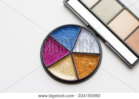 Make Up Beauty Fashion Concept. Bright glitter tinsel palette in a round box and natural eyeshadow palette on white, top view, flat lay