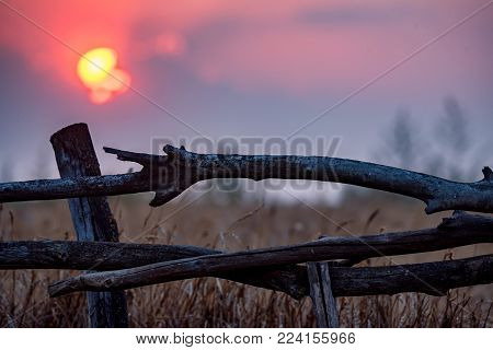 Close up rural wooden fence with beautiful red sky and sunset in field
