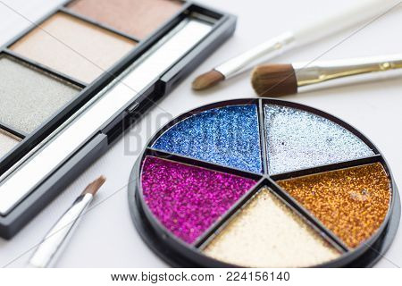Make Up Beauty Fashion Concept. Bright glitter tinsel palette in a round box, natural colors eyeshadow palette and professional brushes on white, close up