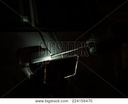 car thief with glove trying to open a vehicle door by screw driver in dark