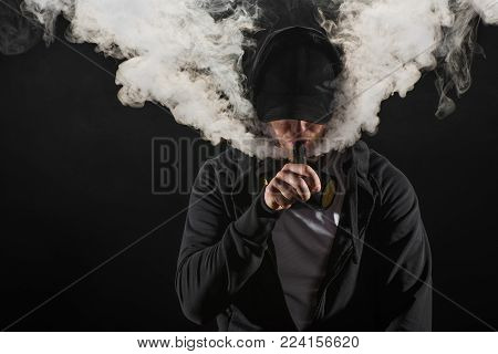 Young bearded man wearing cap exhaling smoke of electronic cigarette isolated on black