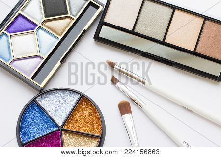 Make Up Beauty Fashion Concept. Daily and evening shimmer eye shadow palette, bright glitter round palette and professional brushes on white, top view