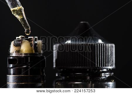 Close-up view of filling electronic cigarette with e-liquid isolated on black
