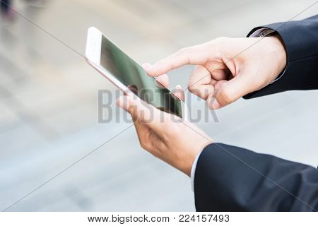 close-up Side view image of male hands using modern smart phone outdoors, hispter man walking at sunny day chatting with friends via cellphone,communication and social network concept