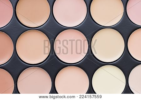 Make Up Beauty Fashion Concept. Background with face make up foundation, concealer and contouring palette in a black box, top view