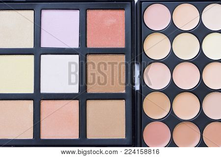 Make Up Beauty Fashion Concept. A set of professional make up essentials: eyeshadows, face foundation, concealer, contouring on black, top view