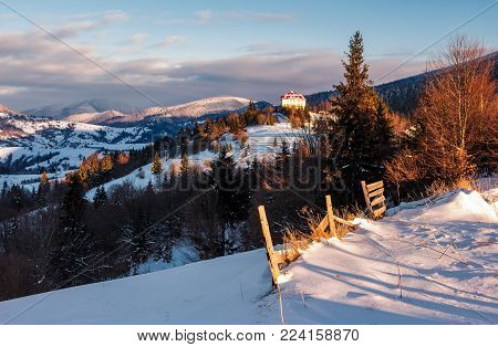 Synevyr, Ukraine - JAN 19, 2016: countryside in Carpathian mountains at sunrise. lovely scenery with wooden fence and coniferous forest on a snowy slopes. hotel and a village on hill in a distance