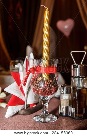 Romantic table setting decoration - golden candle in a glass with coffee seeds on the table near white and red napkins. Love and Romantic concept.