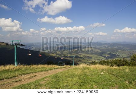 A view to red open cableway cabin over the top of the mountain and buautiful landscapes with blue mountains, green walley