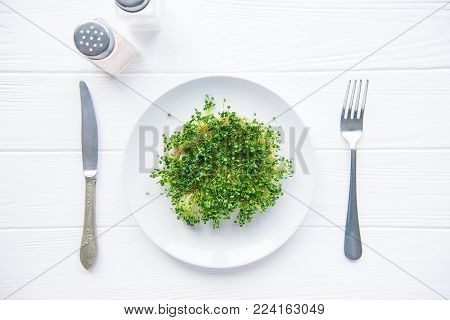 Top view plate with fresh organic sprout micro greens served with cutlery and herbs on the white wooden table. Healthy Raw diet food concept. Copy space for text. Selective focus