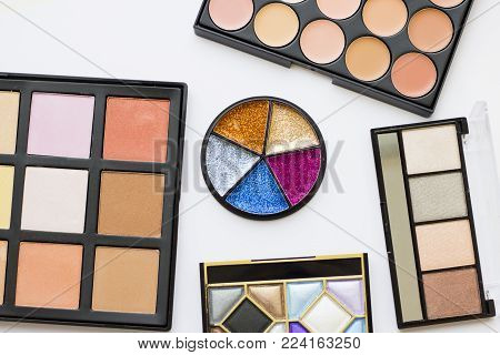 Make Up Beauty Fashion Concept Mock up. A set of professional make up products: eyeshadows, eye and lip glitter, face foundation, concealer, contouring, top view, flat lay